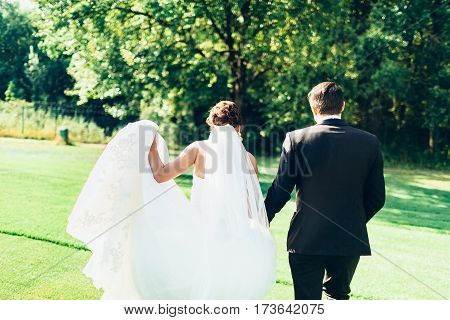 Young couple walk on the green grass of the golf course. The bride and groom are happy to be together. Unrecognisable