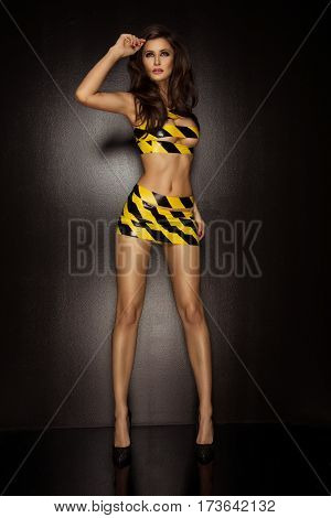Sexy Brunette Woman Wrapped In Yellow And Black Tape