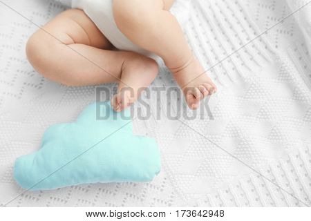 Little baby legs on bed with toy