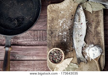 Fresh fish smelt with spices on the kitchen board near the cast-iron frying pan