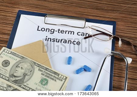 Text LONG-TERM CARE INSURANCE on information clipboard with money, glasses, stethoscope and pills closeup