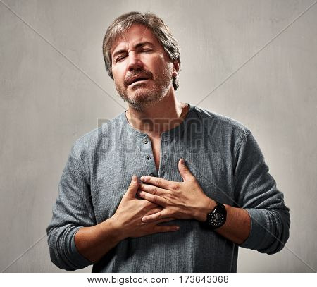 Depressed hurt man portrait over gray wall background