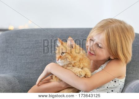 Beautiful little girl sitting on grey armchair with red fluffy cat
