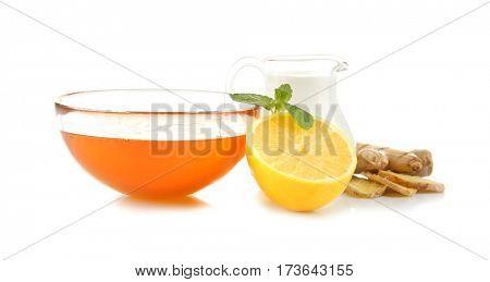 Natural medicine concept. Honey, lemon, milk and ginger on white background