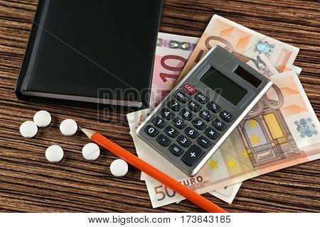 Notebook, money, calculator and pills on wooden background