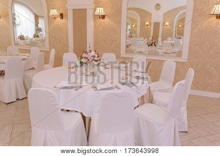 Guest tables with bouquet in luxury decorated wedding banquet room