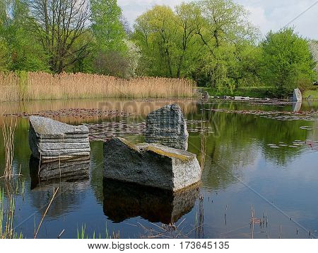 Stones in the pond. Lodz, Poland - April 28, 2015 Stones reflected in the pond in the Botanical Garden in Lodz.