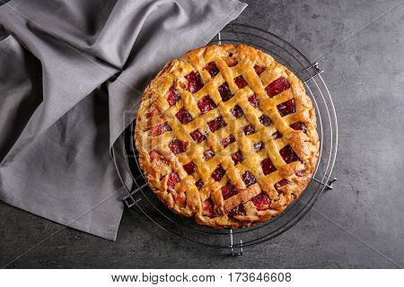 Metal stand with delicious berry pie on gray background