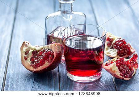 red fruit juice in grass with fresh cut pomegranate on blue wooden table background