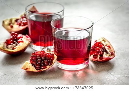 ripe pomergranate and glass of fresh juice on stone table background