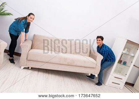 Wife and husband moving sofa couch