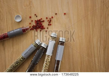A variety of peppercorns in glass tubes.