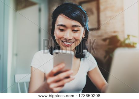 Young smiling Asian woman spending rest time at home on sunny sunday and using smartphone for video conversation with friends.Selective focus. Blurred background, flares effect