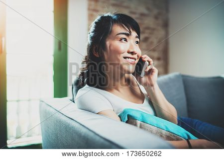 Young smiling Asian woman spending rest time at home on sofa and using smartphone for call her friends.Blurred background, flares effect