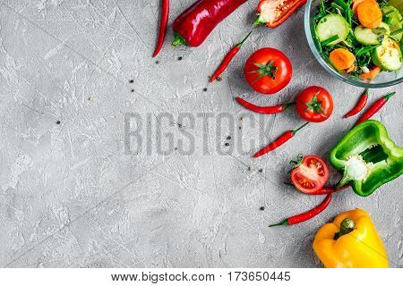 cooking vegetables on the stone background top view.
