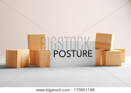 Paper with word POSTURE and wooden cubes on light background