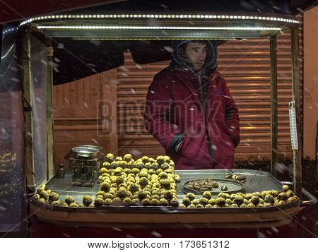 ISTANBUL TURKEY - DECEMBER 30 2015: Picture of an young chestnut seller on a cold winter evening on Istiklal street under a heavy snowstorm