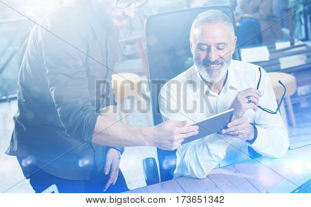 Group of two partners making great idea during work process in modern office.Adult bearded man watching mobile tablet and smiling.Business people meeting concept.Visual effects