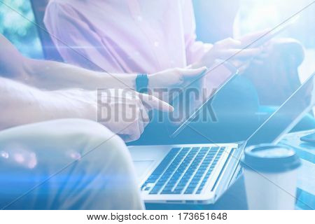 Closeup view of male hand pointing on digital tablet.Young business team working with new startup project.Laptop on the table.Blurred background, visual effect. Horizontal.