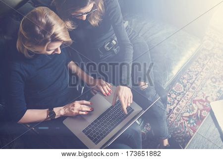 Top view of two young girls working on computer and using mobile devices.Woman wearing black pullover and sitting on the sofa.Horizontal, blurred background, visual effects