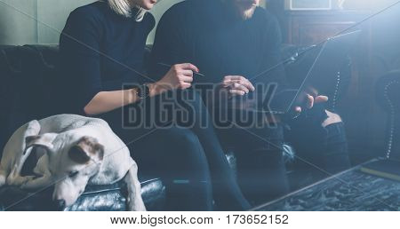 Group of young coworkers making great business decisions.People discussing new project at modern meeting room.Man using laptop, woman smiling, white dog sleeping on sofa. Visual effects, flare.Crop