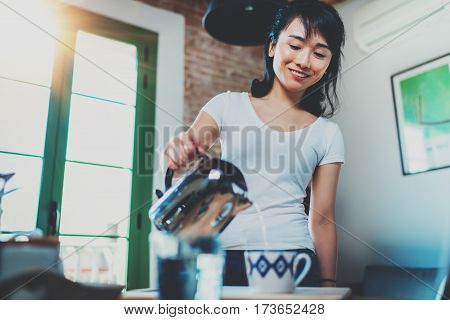 Portrait of young Asian brunette woman using kettle for make tea or black coffee on kitchen at room interior background. Blurred, flares effect