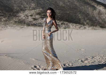 Fashion asian woman model in luxury shiny dress in desert