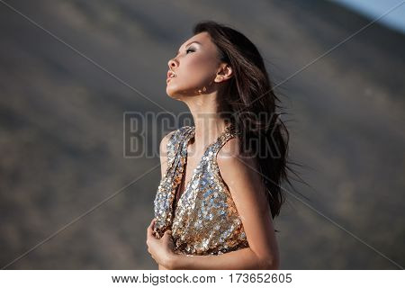 Fashion asian woman model in luxury shiny dress in desert