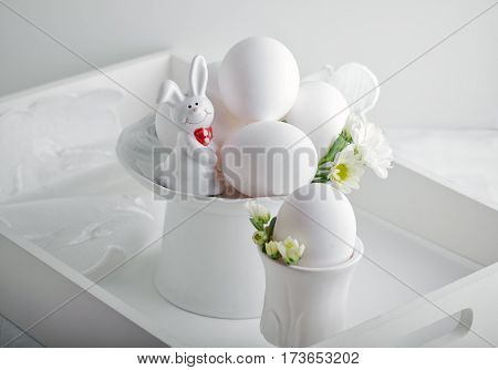 Eggs, rabbit and flowers on a white surface. Easter symbols