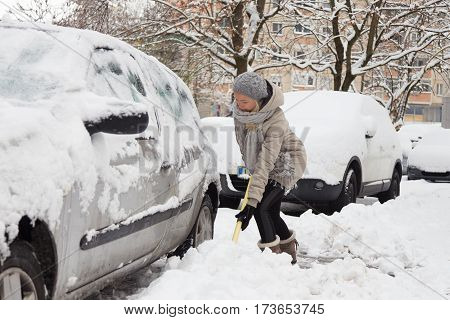 Independent woman shoveling her parking lot after a winter snowstorm.