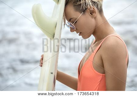 Cute blonde girl with closed eyes stands sideways on the beach and holds the surfboard on the blurry background of the sea. She wears orange swimsuit with sunglasses. Closeup. Horizontal.