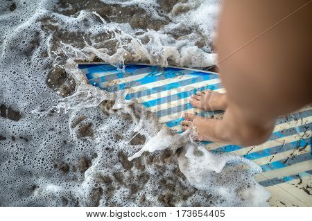 Closeup photo of the female legs which are standing on the light surfboard with gray-cyan stripes in the waves on the beach. Horizontal.