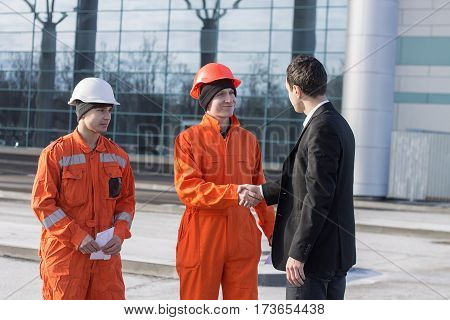 boss or Chief handshaking with workers engineers. Good job. Business modern background