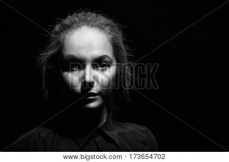 sad woman face on black background, monochrome