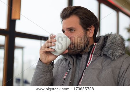 Thoughtful man wearing warm winter jacket looking out the window while getting warmed with coffee with milk.