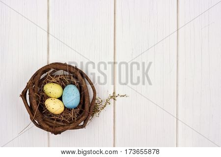 Single Spring Nest With Easter Eggs Over A White Wooden Background
