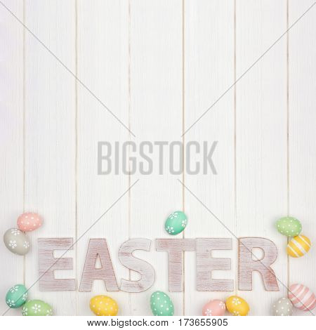 Easter Spelled In Rustic Wooden Letters With Surrounding Easter Eggs Over A White Wood Background