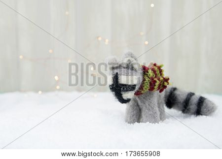 Felt Raccoon Ornament on Snow with subtle bokeh background