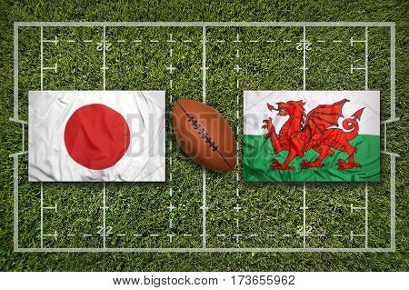 Japan vs. Wales flags on green rugby field, 3 D illustration