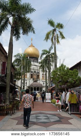 SINGAPORE 12/29/2016 -- Street full of tourists at Kampong Glam neigborhood with Sultan Mosque at the background.