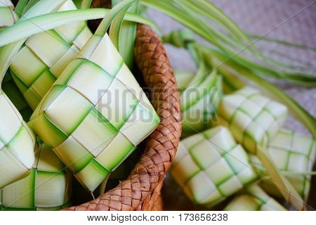 Ketupat (rice dumpling) is a local delicacy during the festive season in Malaysia on traditional mat background. Ketupat, a natural rice casing made from young coconut leaves for cooking rice.