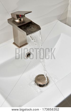Running water from brushed nickel faucet on top of the white modern vanity and marble sink.
