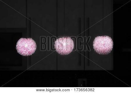 3 lit red metal wired artistic kichen pendant lights in dark background