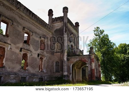 crumbling old castle or a house with vegetation between the stones, bushes and grass, sunny day, blue sky, side view
