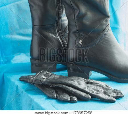 Pair of women's fashion black leather boots and gloves.