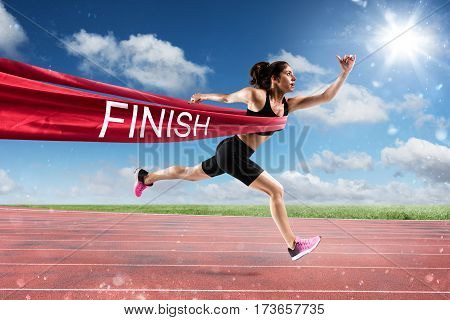 Athletic woman goes beyond the red ribbon at the arrival of a race