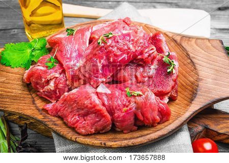 Fresh raw chopped meat beef on an wooden board plate. Raw ingredients spices herbs thyme coriander basil olive oil and vegetables on gray wooden background for raw chopped meat beef.