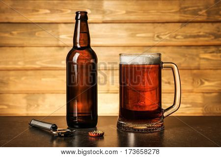 Mug of beer and bottle on table against wooden background