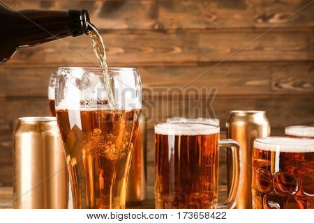 Pouring beer from bottle into glass on wooden background