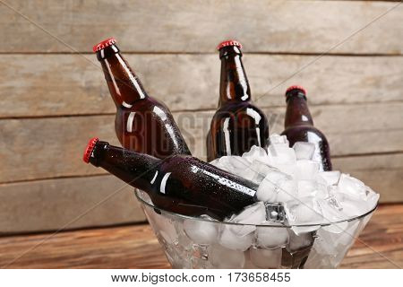 Bowl with bottles of beer in ice on wooden background